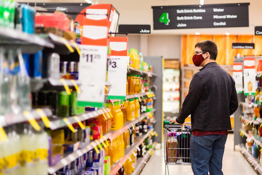 male person walking down grocery store aisle wearing home made face mask during covid-19 pandemic