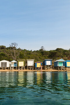 Woman on stand up paddle board in front of  beach huts