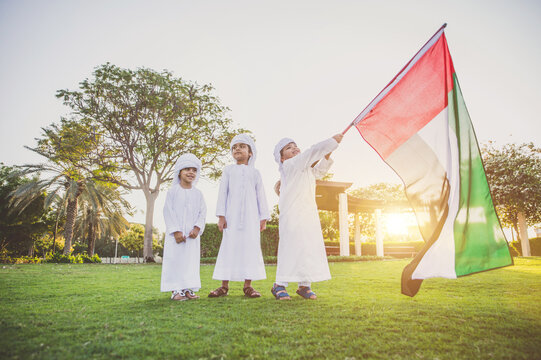 Children playing together in Dubai in the park. Group of kids wearing traditional kandura white dress from arab emirates