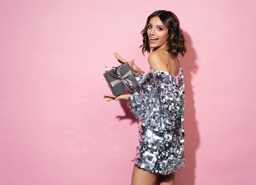Beautiful happy woman wearing sparkle dress with gift box at celebration party. New Year eve celebrating concept