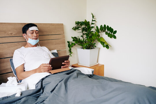 Sick Asian man with cooling gel patch on forehead and medical mask lying in bed with talbet computer when staying home due to coronavirus disease