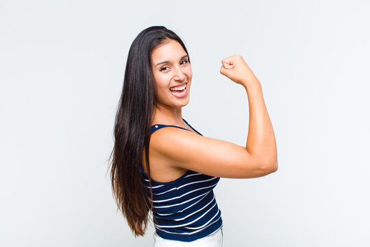 young woman feeling happy, satisfied and powerful, flexing fit and muscular biceps, looking strong after the gym