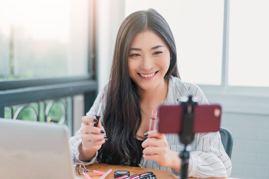 Online beauty online video broadcast vlogger, beautiful Asian woman internet personality content creator marketing sales presenter, makeup products using mobile smart phone computer laptop technology