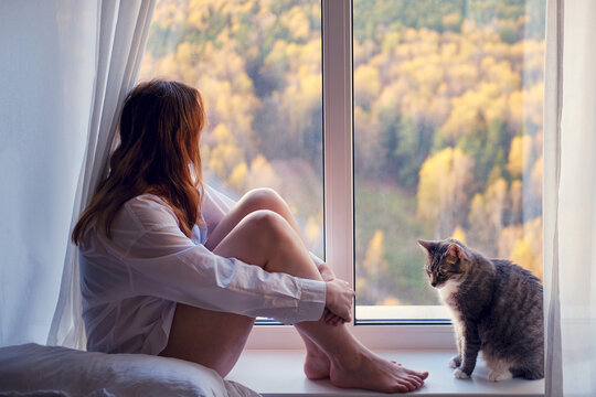 A young woman sits on a window sill in quarantine with pet. Sad autumn weather and home comfort