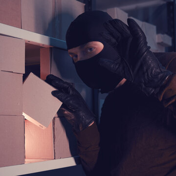 A man in a balaclava steals a box with a parcel in a warehouse at night