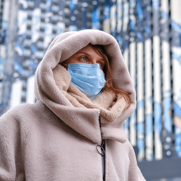 Woman in a medical mask on the background of high houses of the city street