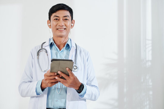 Happy smiling Asian middle-aged doctor with digital tablet wearing earphones to make video call
