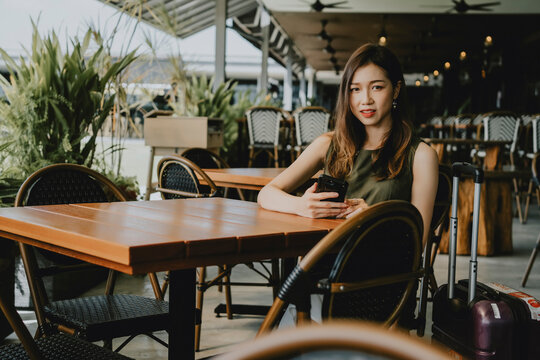 Portrait Of Woman Sitting On Chair At Restaurant