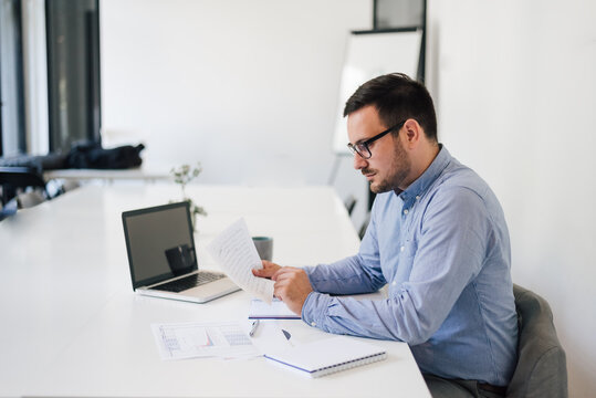 Stressed out businessman in office making important decision about serious problem working under pressure and tight deadline looking at spreadsheet document report account solving bad situation