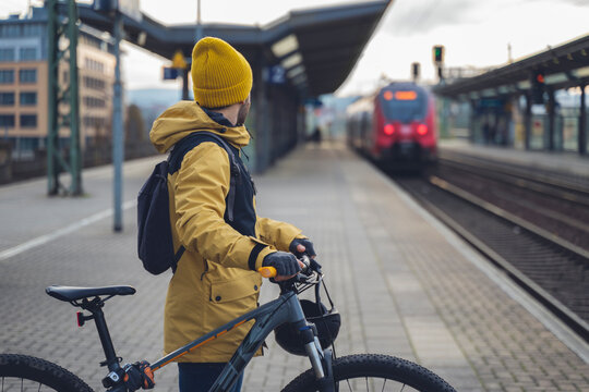 A man in winter clothes, waiting with his bike, the train. In the background the train that is about to arrive.