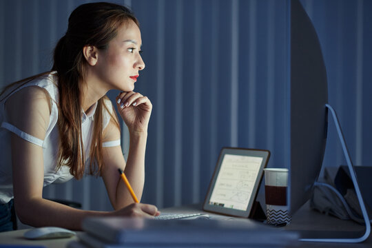 Pensive young female engineer working in dark office, looking at computer screen and taking notes in document