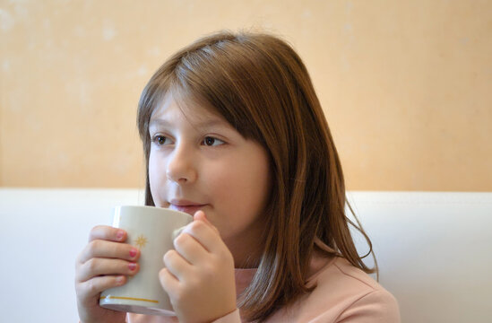 young child is drinking milk on the mug