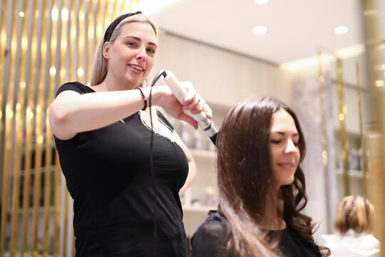 Haircutter making curls for woman