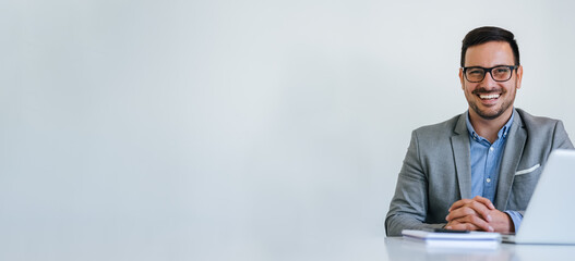 Banner panorama portrait of young smiling cheerful businessman manager entrepreneur with eyeglasses...