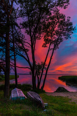 Beautiful colorful sunset over the lake summer landscape with boats on the shore.