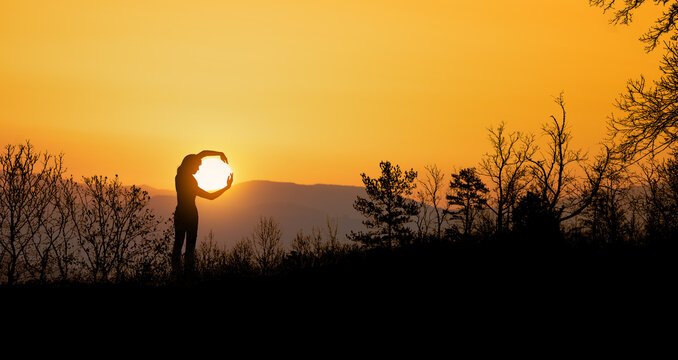 woman catches the setting sun with her arms