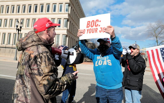A U.S. President-elect Joe Biden's supporter argues with two U.S. President Donald Trump's supporters as the Board of State Canvassers meet to certify the results of the election in Lansing