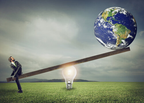 Businessman uses a lightbulb ad lever to lift the World. Earth provided by Nasa.