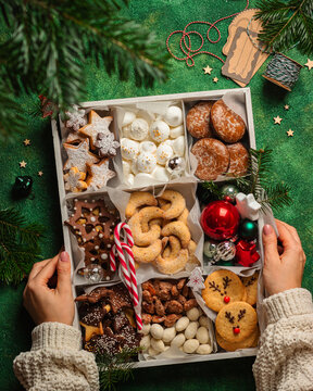 christmas cookies box on green background with girl hands
