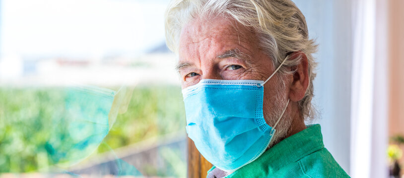 portrait of one old and mature man looking at the camera wearing mask to prevent coronavirus indoors - lockdown lifestyle at home