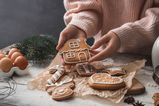 Woman holding delicious homemade Christmas cookie at wooden table, closeup