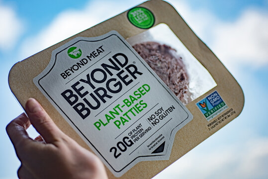 Mclean, VA, USA - July, 9, 2020: Packed Beyond Burger Plant-Based Patties by Beyond Meat in female hand on blurred sky background.