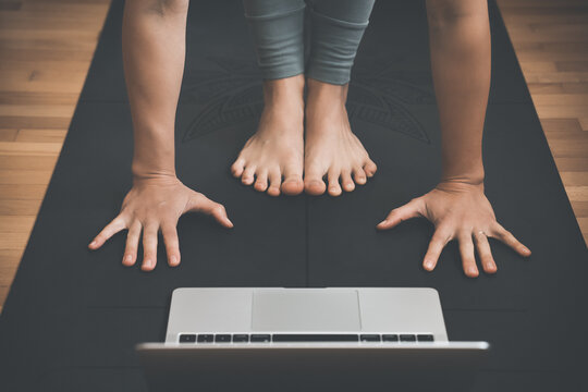 Closeup of female feet and palms on yoga mat with laptop.