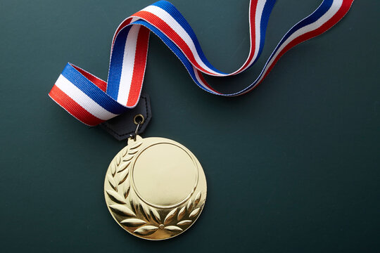 Close-up Of Gold Medal Against Black Background