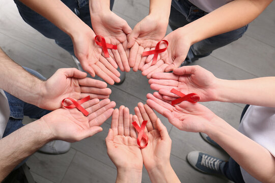 Group of people holding red awareness ribbons indoors, above view. World AIDS disease day