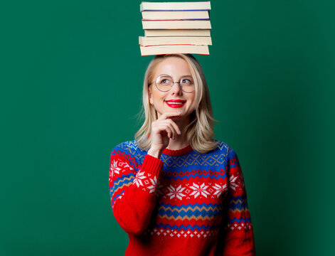 Beautiful woman in Christmas sweater with a books