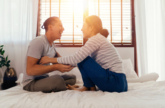 Portrait of happy young adult Asian couple tickling each other on bed together in bedroom interior scene. 30s candid mature husband and wife smiling. Marriage and happy relationship life concept.