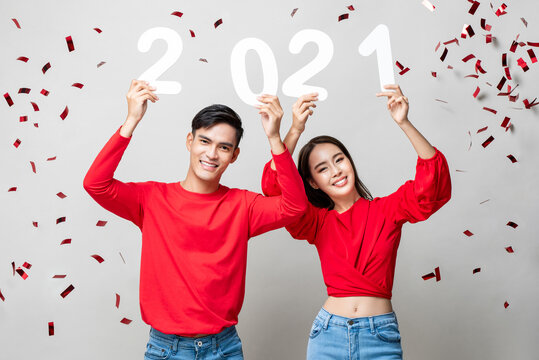 Portrait of smiling happy Asian couple in red casual attire holding 2021 numbers for new year concept on light gray background with confetti