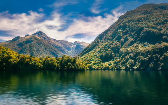 Sunlit mountain range covered in rainforest and reflections in the fjord's water on a beautiful summer day at Doubtful Sound in New Zealand, South Island.