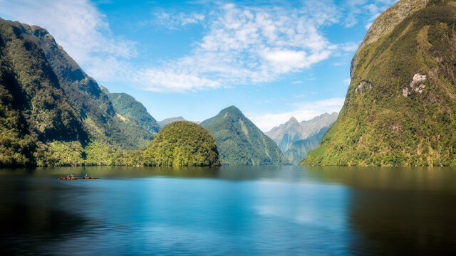 Amazing alpine scenery -including sphere-shaped and pyramid-shaped mountains- in the pristine waters of the fjord at Doubtful Sound with people enjoying water sports in New Zealand, South Island.
