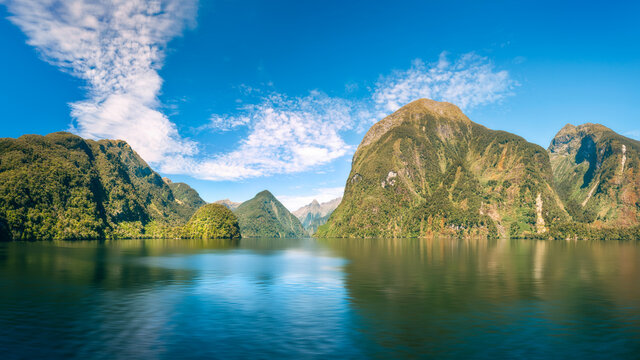 Wonderful sunlit pristine mountain range alpine panorama and reflections in the water in the wilderness at Doubtful Sound in New Zealand, South Island.