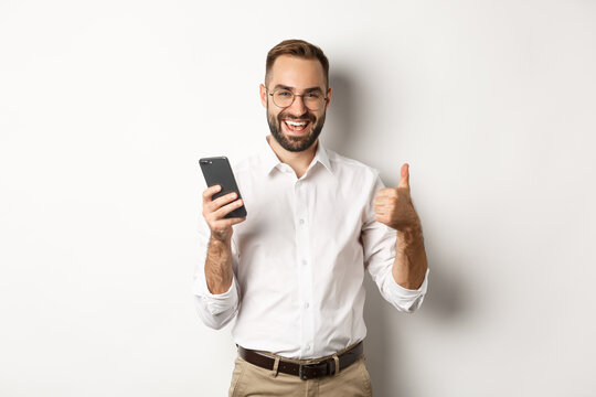 Satisfied business man showing thumbs up after using mobile phone, standing pleased over white background