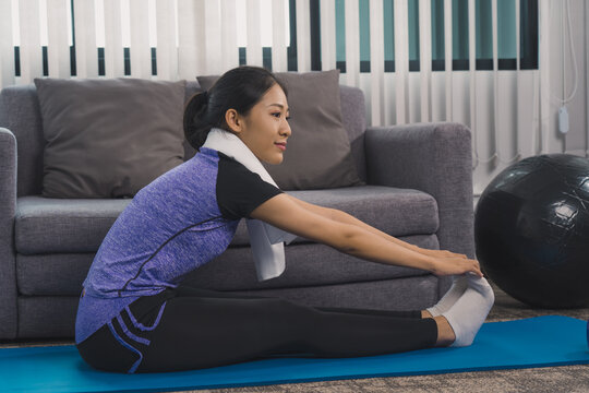 Asian women do stretching exercises after taking yoga classes while at home.