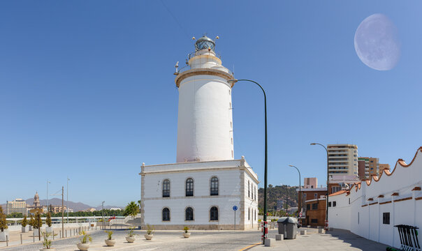 The white lighthouse at the port of Malaga in Andalusia. It's a summer's day with blue skies and the moon can be seen. In the background are city buildings.