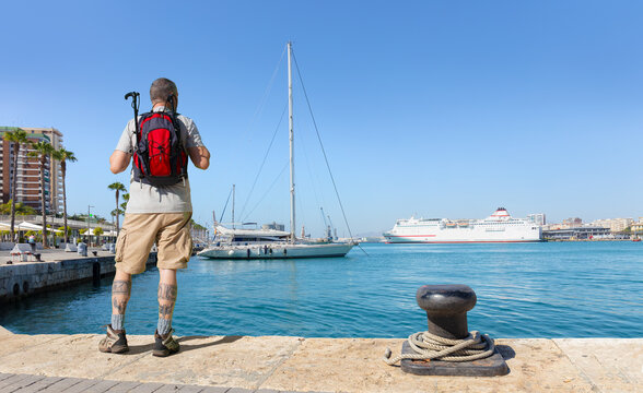 A male hiker with a backpack looks out over the port of Malaga in Andalusia. It's a summer day with blue skies. There are sailboats and a white ferry in the background.