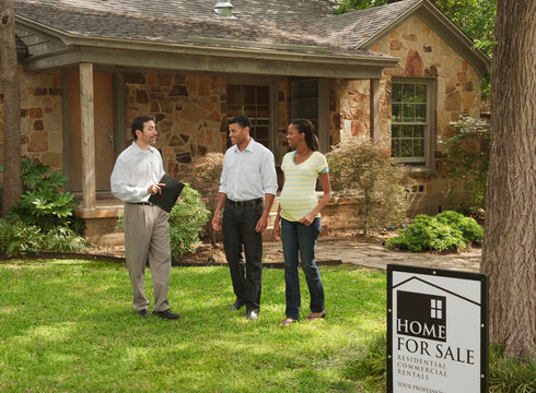 Couple and realtor looking at home for sale