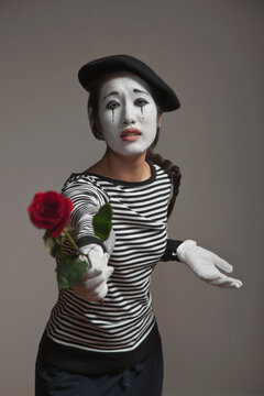 Woman in mime costume holding out rose
