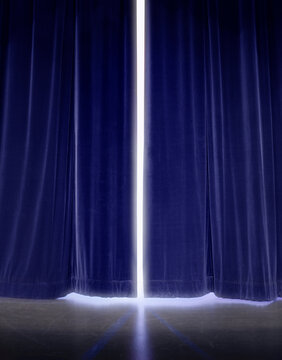 White light glowing though gap in blue stage curtains.
