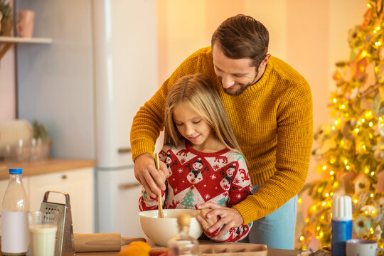 Girl and her dad stirring something in a bowl