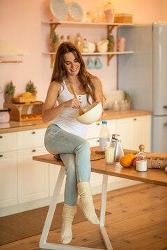 Pretty woman in white tshirt stirring something in a bowl