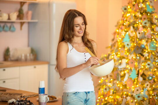 Pretty woman in white tshirt stirring something in a bowl and smiling