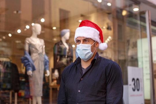 Uomo con cappello da babbo natale, camicia, jeans e mascherina chirurgica,  in centro città tra le vetrine dei negozi
