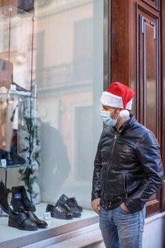 Uomo con cappello da babbo natale, giacca in pelle e mascherina chirurgica,  gira tra le vetrinedi un negozio in centro