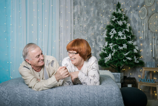 man and woman in christmas. Adult parents Christmas holiday at home. Interior New Year.  Happy mom and dad on the bed in the interior