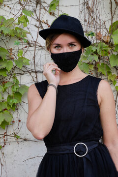Young girl with black hat, black dress and mask for the COVID