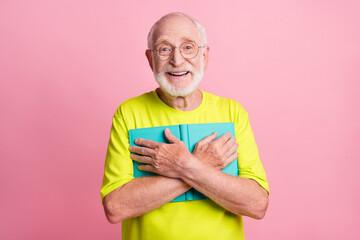Portrait of impressed optimistic pensioner hug copybook wear spectacles green color t-shirt...
